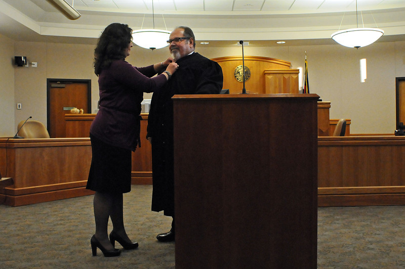 Alexandra Rand buttons up her husband, Judge Robert Rand, following a ceremony to swear him in on Monday at the Larimer County Justice Center in Fort Collins. Judge Rand will fill the vacancy by Judge C. Edward Stirman and will work in Loveland for the next two years.