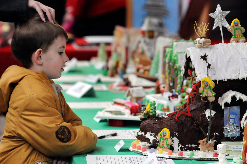 Kristie Crites of Fort Collins touches her six-year-old son, Teagan's head as he looks at a gingerbread house by Loveland artist Blair Muhlestein during the Loveland Lights event at the Loveland Public Library on Sunday. The gingerbread houses were auctioned off to benefit the Firends of the Loveland Public Library's capital campaigne.