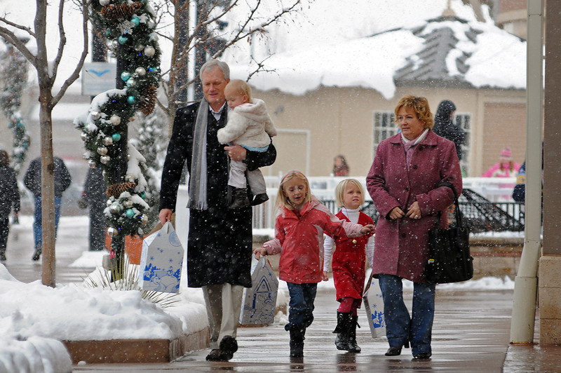 Greg Yancey, left, and his wife Ellen, right, walk the Promenade Shops after buying Christmas gifts for their neices, Vivian Fraser, 1, in Greg Yancey's arms, Olivia Fraser, 7, and Grayson, 4,
