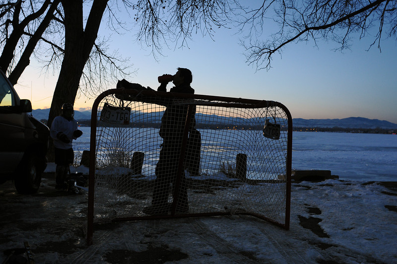 Matt Buffone of Stratford, Conn., rehydrates after he and Jason Ratajczak of Greeley, not in photo, and Isaac Romero of Greeley, left, come off the ice of Lake Loveland on Sunday evening.