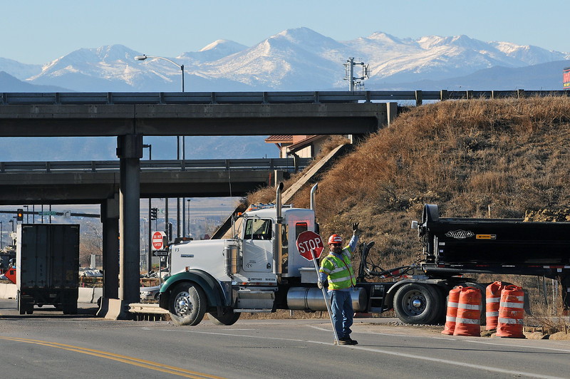 A construction zone flagger, who declined to give his name, controls traffic on Crossroads Boulevard at Interstate 25 on Monday. Construction continues at the interchange as the planning stage of construction gets underway at the interchange of Interstate 25 and US 34 just two miles south.
