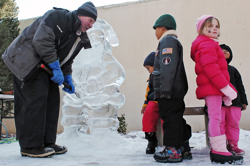 Michael Pizzuto of Denver chats with youngsters while carving an ice sculpture of Santa Claus on Saturday at Thompson Park in downtown Loveland during the Winter Walk event. From left are Pizzuto, Marcus Aguilar, 5, Javier Aguilar, 7, Amanda Rutledge, 5, and Isabella Aguilar, 4.
