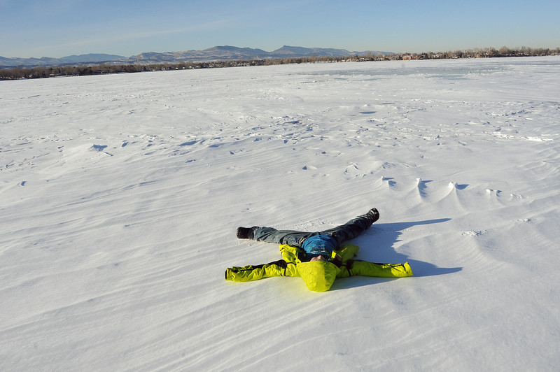 Timothy Grove, 7, of Loveland takes a break from ice fishing with his dad, Bob Grove, and grandfather, Mike Grove, to make a snow angel under a cloudless sky on Lake Loveland. Ice measured at least eight inches in a hole near the area they were fishing.
