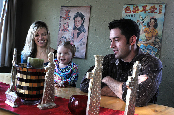 Jacob Fellure, right, and his wife Nicole sit with their daughter Zuri, 10 months, during an interview in their Loveland home. The couple spent a recent vacation in Las Vegas running a marathon and competing on a game show.