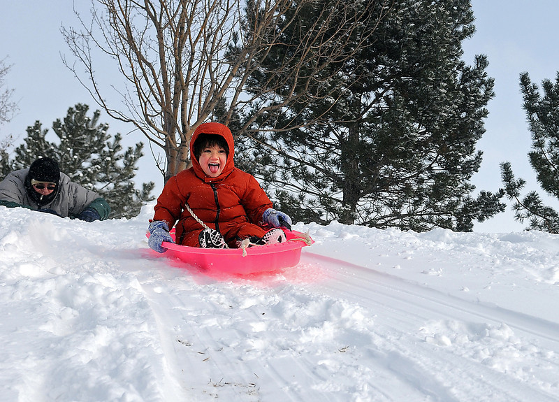 John Gerstenberger of Loveland pushes his daughter Oriana Gerstenberger down a hill  at North Lake Park in Loveland. Gerstenberger took his daughter out to enjoy the  snow  after he picked her up from preschool.