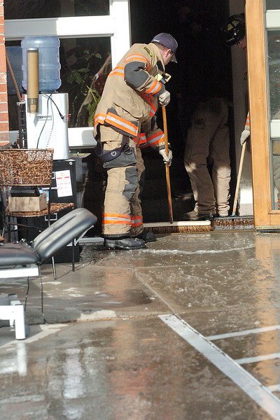 Firefighters with the Loveland Fire and Rescue Dept. use brooms to remove water from the lobby of a building at 2530 Abarr Drive where a fire sprinkler system pipe burst and flooded the building.