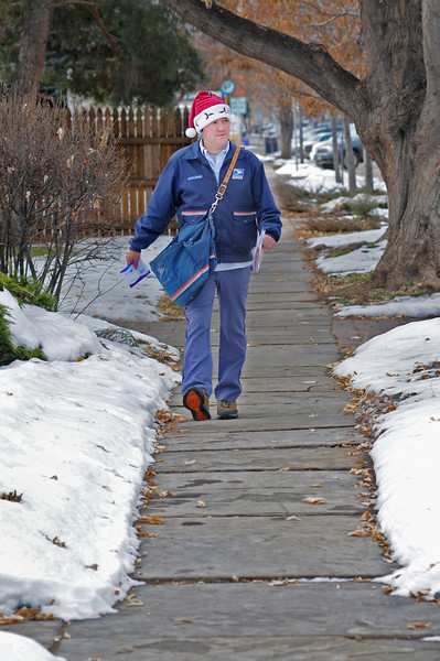 "United States Postal Service Letter Carrier Travis Stevens walks his route eastward along Third Street toward Washington Avenue on Tuesday. ""I love this time of year,"" said Stevens. ""Even though the work load is a bit heavier."""