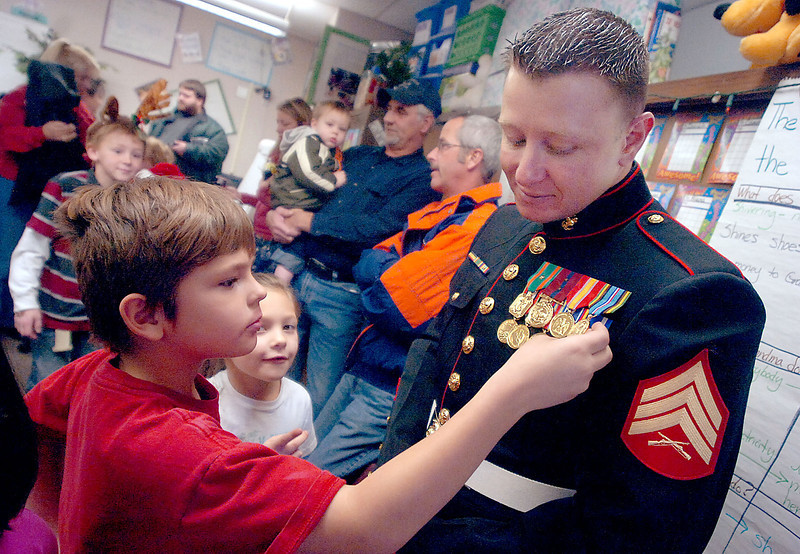 B.F. Kitchen Elementary School  students Cameron Adams, 8, left,  and Lashay Martinez, 7, center,  ask Sgt. Mark Brunick, a 28-year- old Marine from Loveland, about  the medals on his uniform Friday  at school. Students in the second- grade class wrote letters to  Brunick and other troops serving  overseas. While on leave, he  stopped by the school to thank  them for the letters.