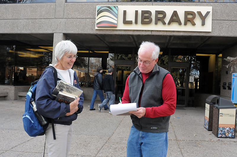 Poudre River Friends of the Library volunteer Lil Price, left, collects a petition signature from Calvin Dewey outside the main branch of the Fort Collins Library, 201 N. Peterson St., on Friday afternoon. Petitioners hope to pass a city ordinance to allow the library to be expanded down  from existing overhangs on the building.