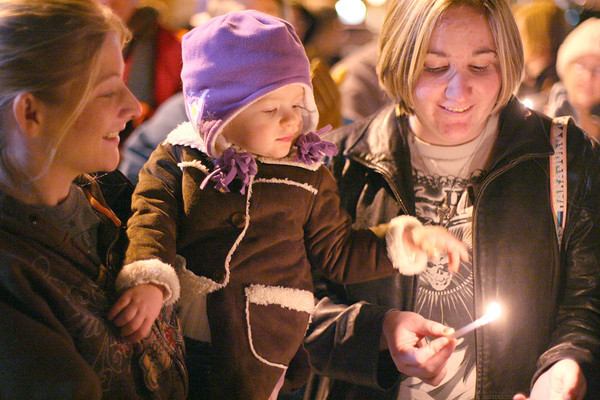 Rebecca Huseby holds her daughter Savanah, 2, while sister, Melissa Huseby holds a candle during Loveland's Menorah lighting Monday night at Peter Park. Photo by Gabriel Christus