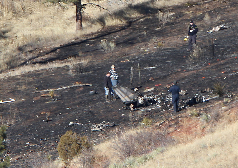 Investigators sift through the wreckage Tuesday, of a Cessna that crashed on Monday south of Carter Lake where Chimney Hollow Reservoir will be built. One person was killed in the crash, but his identity has not yet been released.