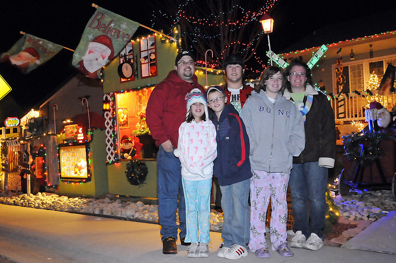 Members of the Lopez family, from left, Scott, Sierra, 8, Jaiden, 10, Cody, 17, Hailey, 11, and Cami pose in front of their home Friday evening that has numerous Christmas decorations in the yard.
