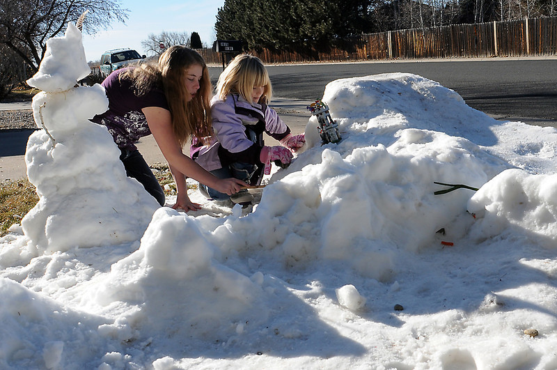 Taylor Dewey, 13, left, and her sister, Abby, 7, play together Tuesday morning in a pile of snow in the front yard of their home in southwest Loveland.