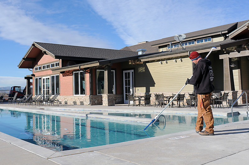 Lake Vista Apartments maintenance technician Brian Barbre cleans the bottom of the pool outside of the complex's clubhouse located at 2235 Rocky Mountain Ave. on Tuesday afternoon.