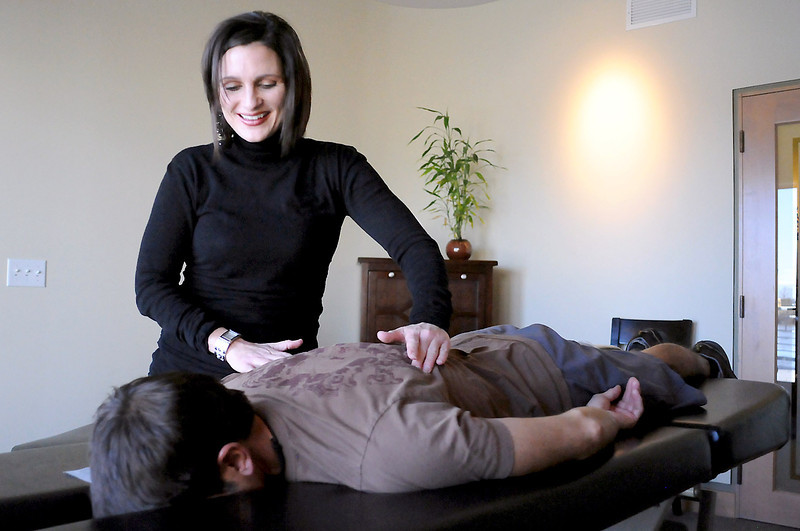 Abarr Lake Chiropractic and Acupuncture Clinic owner Amy Reeves performs a chiropractic adjustment to Craig DeMartino during an appointment Tuesday. Reeves will move her business into a new building she had constructed at 2692 Abarr Drive after a broken pipe flooded the offices she had been leasing last year at another location.