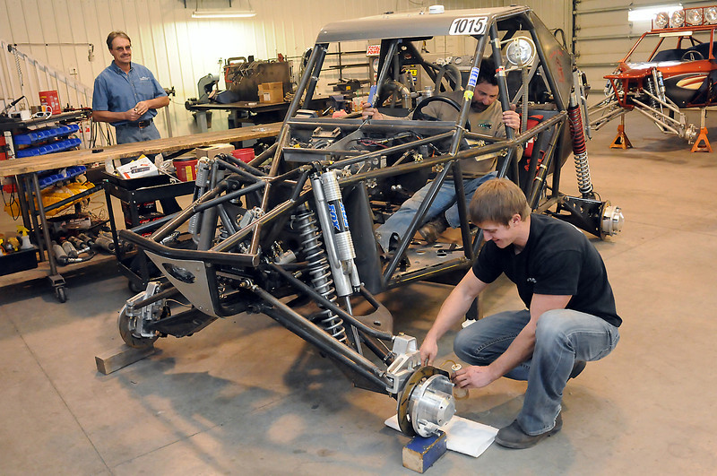 Tom Frank, left, looks on while Troy Dees, right, works on the brakes of an off-road vehicle with the assistance of Shane Ellis on Dec. 17, 2010 in the workshop at Franks' business, Colorado Sandcars in Windsor. Frank and Dees are members of a team racing in the 2011 Dakar Rally which starts New Year's Day in Argentina and runs for two weeks.