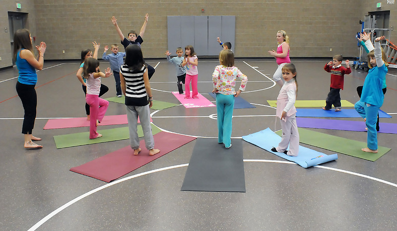 Yoga instructor Amy Norris, left, explains the rules to the game musical mat during a yoga class for kids on Wednesday afternoon in the gymnasium at Ponderosa Elementary School. The game is similar to musical chairs, but instead of sitting in a chair when the music stops participants must perform a yoga pose on a mat.