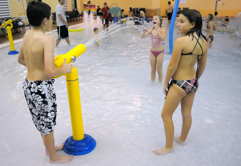 Austin Sobraske, 11, left, squirts Danielle Sobraske with a water gun while Sadie Greenstien looks on as they play together in the Chilson Recreation Center's new pool area on Tuesday, Dec. 21, 2010.