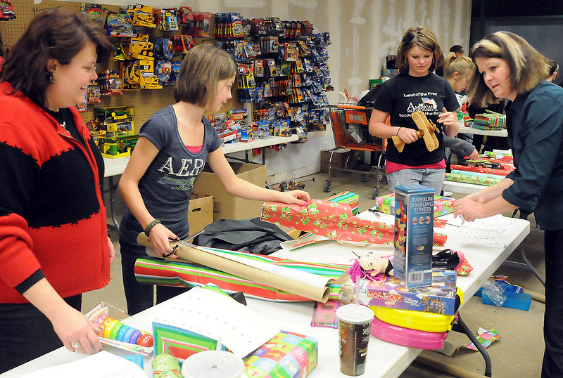 Volunteers wrap select and wrap Christmas gifts Wednesday evening at the Loveland Outlet Mall that will be distributed to needy families through the Santa Cops program. From left are Deanna Sloat, Jill Klinger, 13, Karli Klinger, 15, and Katie Klinger.