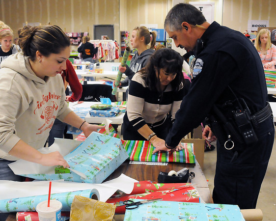 Loveland Police Officer Jim Betrus, right, wraps Christmas gifts with his daughter, Kim, left, and wife, Connie, during a volunteer night for police department employees and their families to help out with the Santa Cops program.