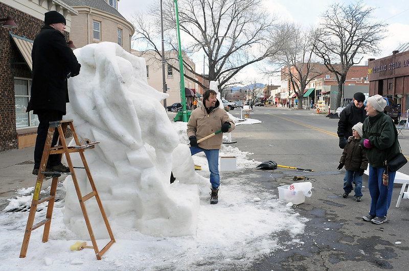 "Snow sculptors Justin Bashor, left, and Stefan Kleinschuster work together on a piece called ""Starman"" as part of the Sculpture in the Dark event in downtown Loveland.  At right are Loveland residents Ruth and Jerry Portugal and their grandson, Luke Portugal, 7, who was visiting from Highlands Ranch."