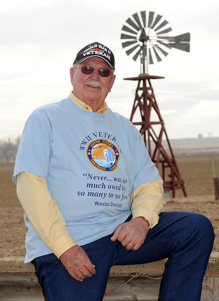 World War II veteran Sam Macdonald poses Dec. 23, 2010 at his home in front of a windmill he built in 1998 on his property southeast of Berthoud.