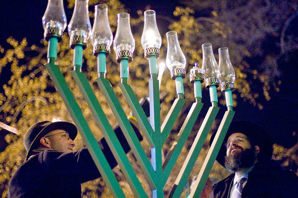 Greg Kindred lights a candle in the menorah while Rabbi Yerachmiel Gorelik looks on during Loveland's Menorah lighting on Monday night at Peter Park. Photo by Gabriel Christus