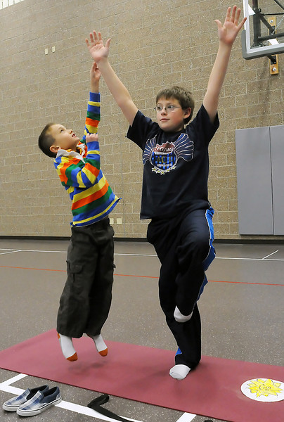 Eight-year-old Stavie Didier, left, leaps up to pick an imaginary apple while Stone Foster, 10, holds the tree pose during a yoga class for kids on Wednesday afternoon at Ponderosa Elementary School taught by Amy Norris.