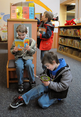 Seven-year-old Zion Albrecht, left, and his brother, Jack, 5, read books in the children's section of the Loveland Public Library on Saturday while their cousin, Brandon Ricks, 6, looks at books on display.