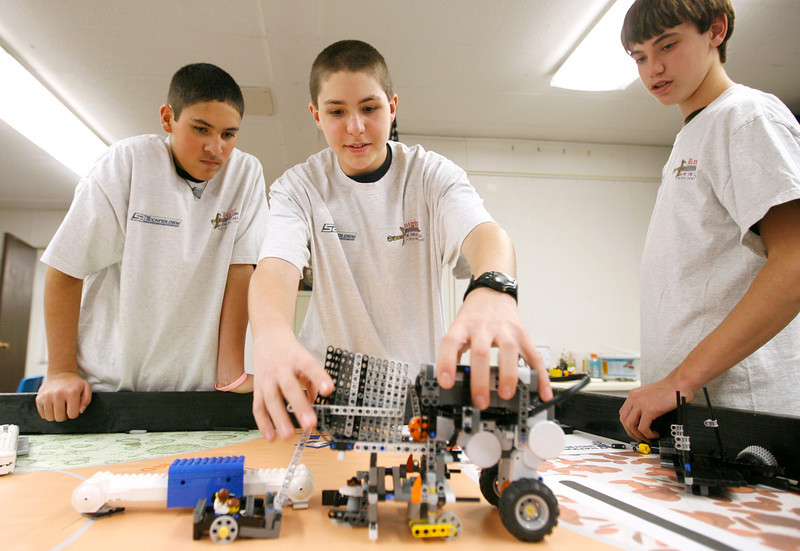 Daniel Probasco, 14, moves their Lego robot back to base while Cody Marvin, 14, left and Patrick Canney, 14, watch druing a practice session on Monday at Walt Clark Middle School. Their team, Knights of the Field Table, will be competing in the First Lego League State Championship on Saturday. Photo by Gabriel Chritsus