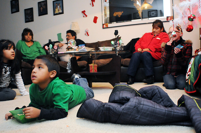 Alejandro Cruz, 7, front, eats a bowl of cereal as he watches television Dec. 17, 2010 in his Loveland home with, back from left, India Cruz, 8, Irene Cruz, Alfred Cruz, Teresa Sirio and Kalli Tikka, 10.