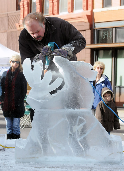 "Craig Winter uses power tools to carve a reindeer sculpture out of a blocks of ice provided by Loveland-based Struckman Sculpture Ice during a demonstration Saturday afternoon as part of the Sculpture in the Dark event. For more information visit  <a href=""http://www.struckmansculptureice.com"">http://www.struckmansculptureice.com</a>."