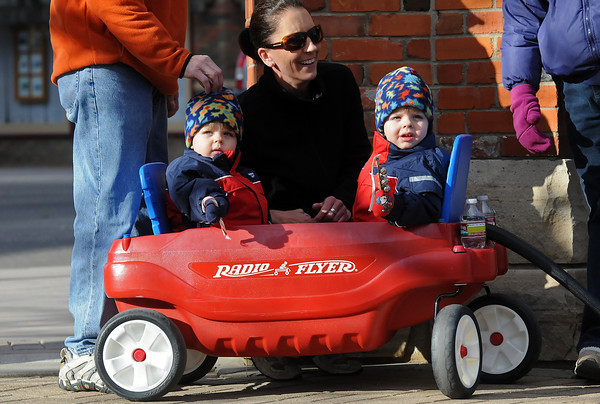 Two-year-old Liam O'Prey, left, holds a candy cane while his twin brother, Aidan, shakes some bells while they and their mom, Kristen, listen to trombone players performing the song Jingle Bells on Saturday during Winter Walk in downtown Loveland.