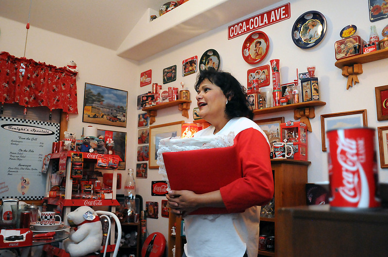 Victoria Villavicencio is surrounded by her assortment of Coca-Cola collectibles and memorabilia as she talks about the various items Wednesday in her Loveland home.