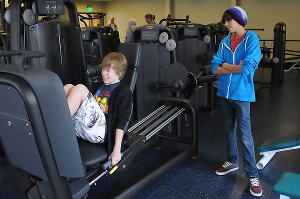Levi Wake, 13, right, looks on while Chase Hildebrandt, 12, works out on the new leg press machine in the weight room at the Chilson Recreation Center during the facilities grand re-opening celebration on Saturday.