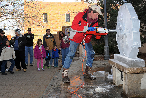 """Spectators watch as ice sculptor Steve Mercia uses a chainsaw to carve a snowflake pattern into a block of ice Saturday afternoon at Thompson Pocket Park. Mercia will participate in the Sculpture in the Dark event on Dec. 11-12 in downtown Loveland where five teams are signed up to create massive sculptures out of snow. The event will also include a parade of lights, sleigh rides with Santa and art workshops. Visit  <a href=""""http://www.engagingloveland.org"""">http://www.engagingloveland.org</a> for more information."""