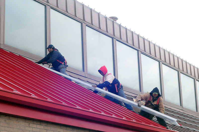 Workers with Colorado Custom Metal out of Denver, from left, Gil Gomez, Omar Bonce and Miguel Cervantes install a metal roof on the north side of Key Bank at Seventh Street and Cleveland Avenue in downtown Loveland on Tuesday.