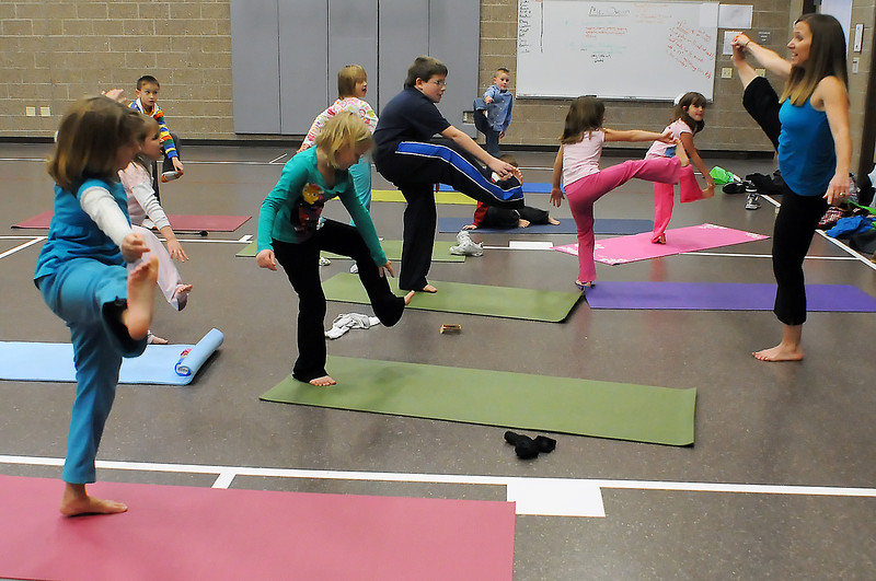 Yoga instructor Amy Norris, right, leads youngsters in a yoga class for kids on Wednesday afternoon in the gymnasium at Ponderosa Elementary School.