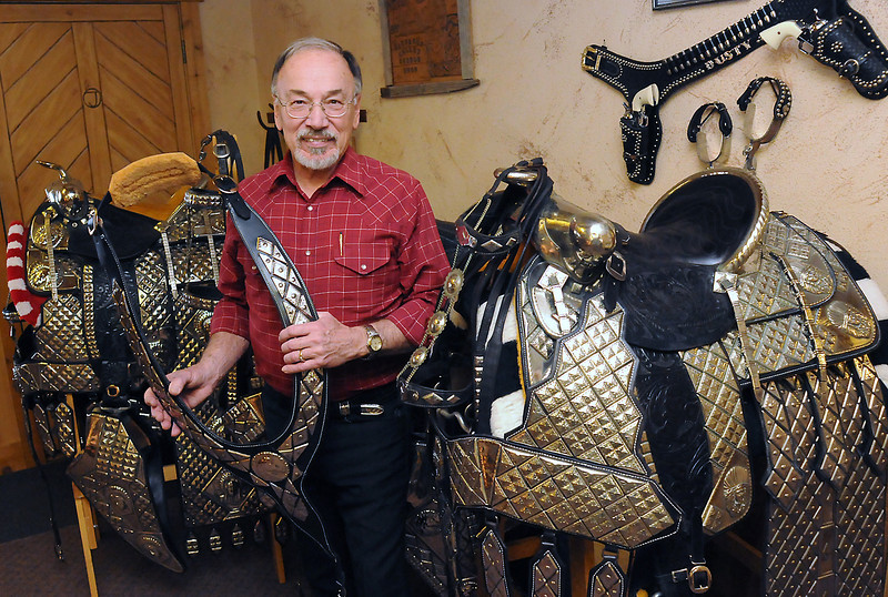 Loveland saddlemaker Dusty Johnson stands in front of some silver saddles in his workshop Wednesday as he holds a martingale that he's restored along with many silver saddles over the years.