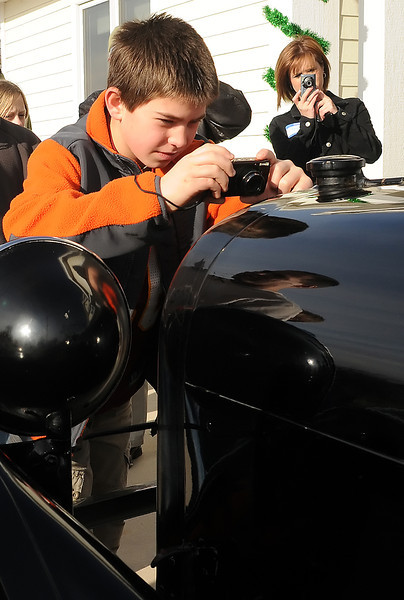 "Ten-year-old Kyle Hecker takes a picture of the front of a 1919 Dodge Brothers touring car Friday, Dec. 24, 2010 in Johnstown after the car was delivered to Keith and Marilyn Smith's house. The car was used in the filming of the 1946 classic Christmas movie ""It's a Wonderful Life."""