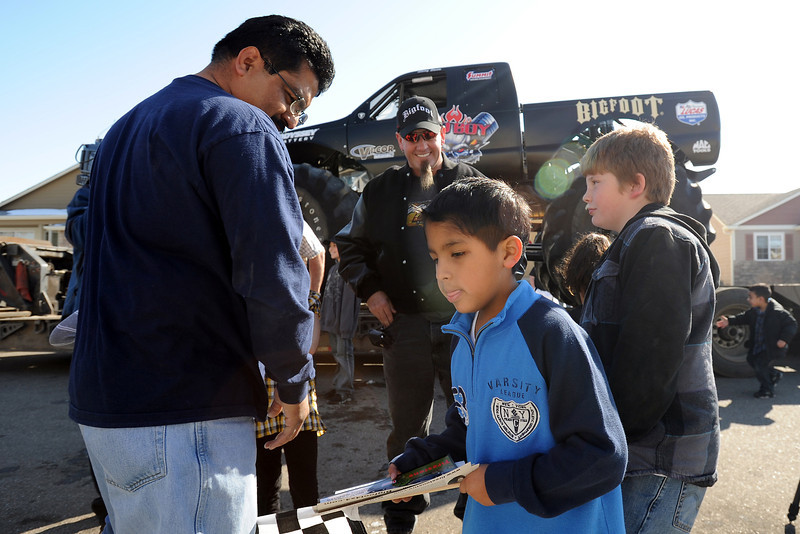 Eight-year-old Alejandro Cruz, front, gets a visit from monster truck driver Larry Swim, center back, who stopped by Thursday afternoon with the monster truck Bigfoot outside Alejandro's home in Loveland.