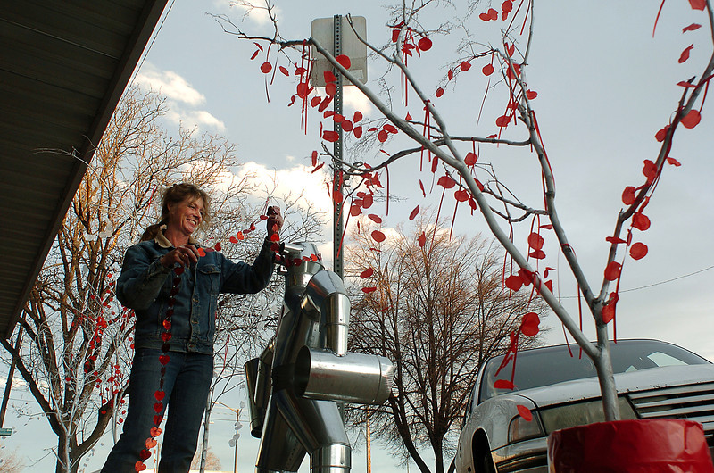 Stephanie Ortega drapes a string of hearts around a tinman Monday outside of a building on the 100 block of West Fourth Street that houses His Place Coffee Shop and Cafe, The Goldsmith jewelry store and King Storage in downtown Loveland. Ortega was decorating for the Sweetheart City Business Decorating contest, organized by the Loveland Chamber of Commerce, which will will be judged by members of the public who can register votes online, with text messages or with paper ballots. Photo by Jenny Sparks