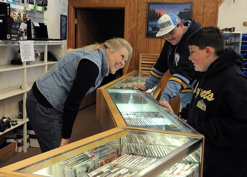 Pam Liebl, an employee at Friendly Pawn, helps customers Dalton Shannon, 16, center, and his little brother Tyler Shannon, 11, Monday in Loveland. Liebl has worked at the pawn shop for 20 years. Photo by Jenny Sparks