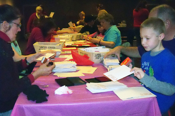 Novice stampers learn how to hand stamp cachets and cancellations on valentines during a stamp camp Saturday for LovelandÕs Valentine Remailing Program.
