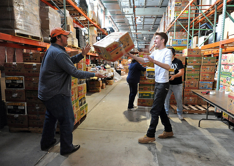 Jason Aldridge, from Belgium, right, tosses a box of clothes to Nick DeCarlo, from North Carolina, left, Tuesday while working at the H.E.L.P International warehouse in Loveland. Aldridge and DeCarlo worked with a large crew of volunteers with the non-profit organization Up With People to get a shipment of donations ready to go to Isreal. Photo by Jenny Sparks