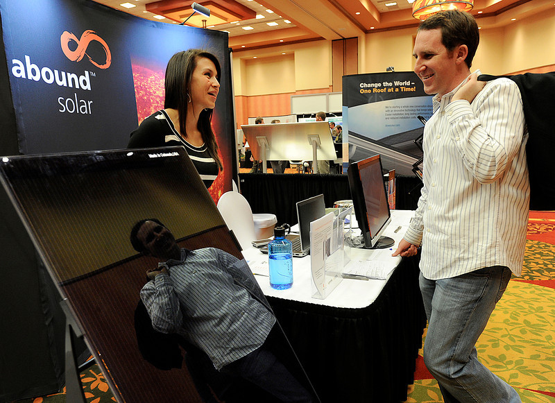 Kim Doll, left, sales associate with Abound Solar, chats with Jake DiRe with Solmax Thursday during the Solar Power Colorado energy conference and expo at Embassy Suites in Loveland. Photo by Jenny Sparks