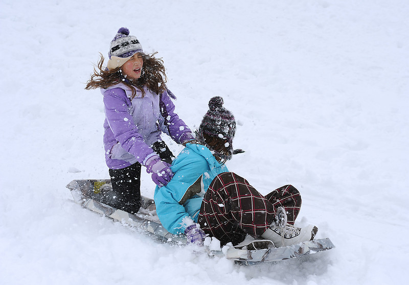 Cristina Romero, 11, front, and pal Megan Voeller, 11, fly down the hill on a sled Friday in Loveland.