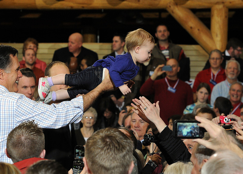 Mitt Romney reaches over the crowd to give 11 month-old Madison Busch of Loveland back to her mother Julie Busch Tuesday during a presidential candidate rally at RV America in Johnstown.
