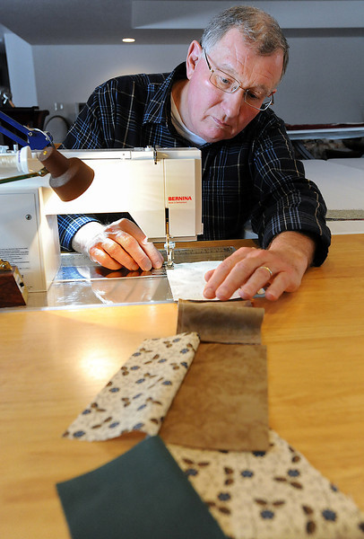 Dave Wieland sews patches of material together while working on a quilt Wednesday at his Loveland home. He is among the few men who have taken up the hobby of quilting in the last 20 years.<br /> Photo by Jenny Sparks
