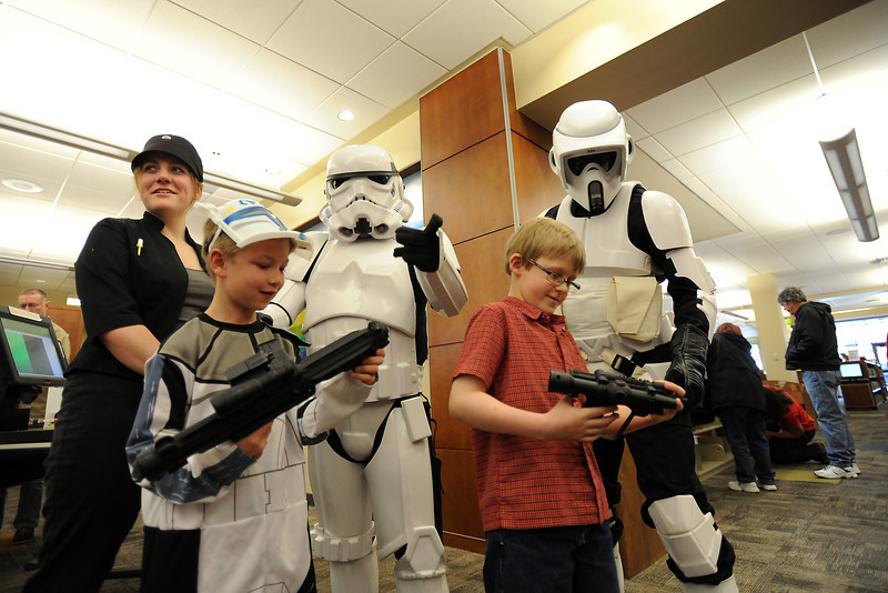 "Zane Acton, 8, front left, and his friend Isaac Johnson, 8, check out the blasters belonging to actors dressed as Star Wars characters during the Loveland Public Library's grand reopening event Saturday, Feb. 18, 2012. At rear from left are Meghan Buckley as Juno Eclipse, Ed Litter as a storm trooper and J Kirby dressed as a biker scout. The Star Wars characters were a big hit with library visitors and Zane exclaimed, ""This is awesome. I just love this."""